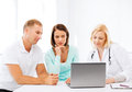 Doctor with patients looking at laptop healthcare medical and technology concept Royalty Free Stock Photography