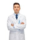 Doctor with prostate cancer awareness ribbon healthcare profession people and medicine concept male in white coat sky blue Royalty Free Stock Photography