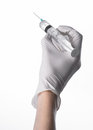 Doctor s hand holding a syringe white gloved hand a large syringe medical issue the doctor makes an injection background Royalty Free Stock Image