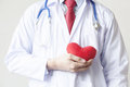 Doctor showing compassion and support holding red heart onto his chest in his coat Stock Photography