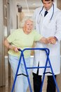 Doctor showing way to the patient using walker young male Royalty Free Stock Photo