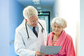 Doctor shows female elderly patient results while standing in hospital corridor Royalty Free Stock Image