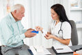 Doctor shows the patient how to use daily dose pills female and senior man Stock Photo