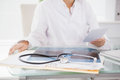 Doctor sitting at her desk with laptop and files Royalty Free Stock Photo