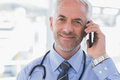 Doctor speaking on the phone smiling Royalty Free Stock Images