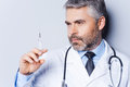 Doctor with syringe confident mature holding and looking at it while standing against grey background Stock Photo