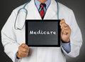 Doctor with tablet computer medicare closeup of a holding a a chalkboard screen the word man is unrecognizable Royalty Free Stock Photo