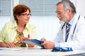 Doctor talking to his female patient senior at the office Royalty Free Stock Images