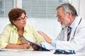 Doctor talking to his female patient senior at the office Royalty Free Stock Photos