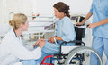 Doctor talking to a patient in wheelchair at hospital side view of female the Royalty Free Stock Image