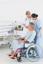 Doctor talking to a patient in wheelchair at hospital side view of male the Royalty Free Stock Photography