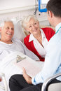 Doctor talking to senior couple in UK Hospital Stock Photo