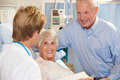 Doctor Talking To Senior Couple On Ward Stock Photo
