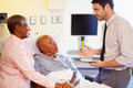 Doctor talking to senior couple on ward holding clipboard looking at each other Royalty Free Stock Images