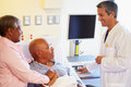 Doctor talking to senior couple on ward in hospital room smiling at each other Royalty Free Stock Photos