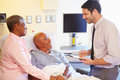 Doctor talking to senior couple on ward whilst taking notes clipboard Stock Image