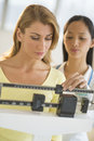 Doctor weighing female patient on weight scale mid adult balance in clinic Stock Photo