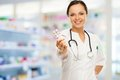 Doctor woman in drug store young positive brunette holding pills Stock Images