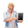 Doctor woman holding tablet computer surprised shows finger to it Royalty Free Stock Image