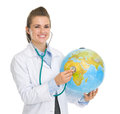 Doctor woman listening globe with stethoscope Stock Photos