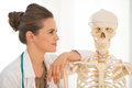 Doctor woman looking on human skeleton portrait of medical anatomical model Stock Photos