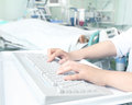 Doctor working at computer in patient's room Royalty Free Stock Photo