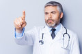 Doctor working on transparent wipe board mature grey hair touching with finger while standing against grey background Stock Image