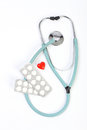Doctors blue stethoscope, pills and one small red heart on white background Royalty Free Stock Image
