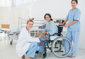 Doctors with female patient in wheelchair at hospital side view of the Stock Photo