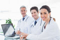 Doctors with laptop smiling at camera in medical office Royalty Free Stock Photography