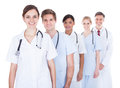 Doctors and nurses in a row happy standing over white background Stock Photography