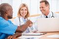 Doctors shaking hands two cheerful while sitting together with female doctor Royalty Free Stock Images
