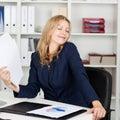 Documenti di fanning herself with della donna di affari allo scrittorio Immagini Stock