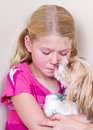 Dog licking childs face sad child sitting in corner with her trying to comfort her Stock Image