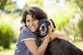 Dog lover with labrador retriever a middle aged female and her black at a park Stock Images