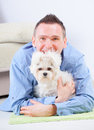 Dog and owner little maltese laying with his on the floor in home Stock Images