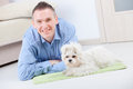 Dog and owner little maltese laying with his on the floor in home main sharpness focus is on the Royalty Free Stock Photography