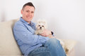 Dog and owner little maltese sitting with his on the sofa in home Royalty Free Stock Image