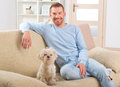 Dog and owner little maltese sitting with his on the sofa in home Stock Photos