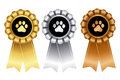 Dog show winner ribbon rosette golden silver and bronze award rosettes for st nd and rd place winners with paw print on center Stock Photos