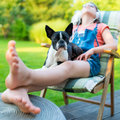 Dog and teenage girl resting in the garden Royalty Free Stock Photo