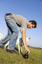 Dog trainer placing a chew toy on the grass at the park with the bull terrier next to him looking at what he s doing with Stock Image