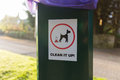 Dog waste clean up sign on plastic trash can Royalty Free Stock Photo