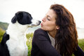 Dog and woman kiss love cute friendship with her pet on travel to coast Stock Images