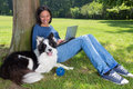 Dog and working girl on her laptop in the park her waiting to play with a ball Royalty Free Stock Photos