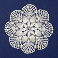 Doily noniesdecies handmade on blue background Royalty Free Stock Photos