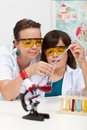 Doing a chemistry experiment at school boy mixing two chemicals helped by his teacher Stock Image