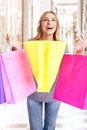 Doing purchase cheerful young female enjoying her in luxury shopping centre happy girl carrying colourful paper gift bags Stock Image