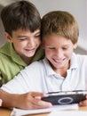 Dois Young Boys que jogam com um jogo video à mão Imagem de Stock Royalty Free