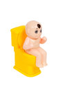 Doll, baby toy sit on toilet bowl, isolated on white background Royalty Free Stock Photo